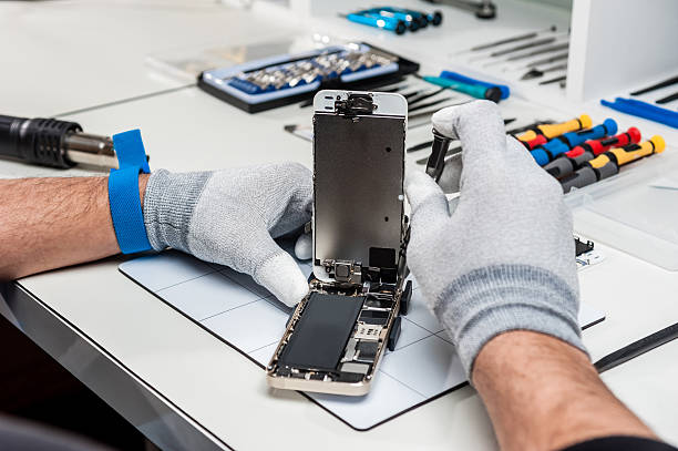 Image of an Apple iPhone being repaired next to a collection of iPhone repair tools