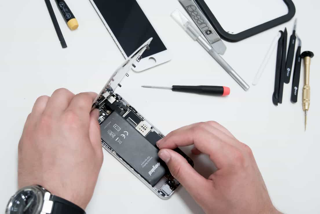 Image of an iPhone being repaired next to a collection of iPhone repair tools