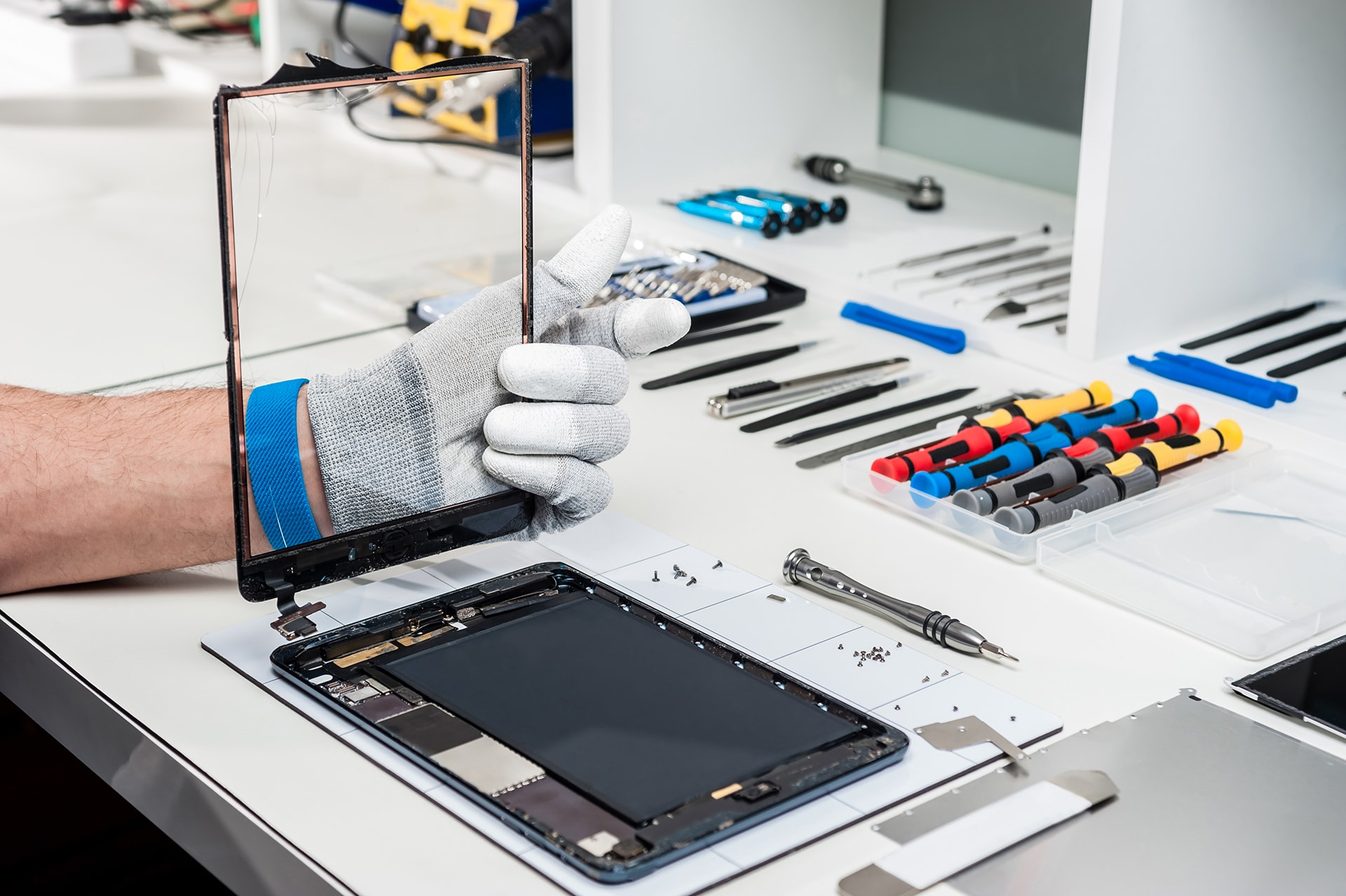 Image of an iPad being repaired next to a collection of iPad repair tools